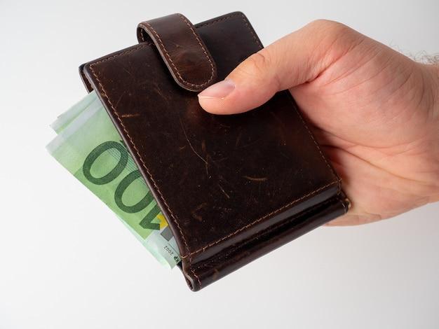 La main d'un homme tient un portefeuille en cuir marron avec des billets de 100 euros qui en sortent sur un fond blanc. le concept d'argent, de richesse, de richesse