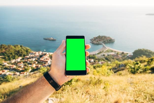 La main de l'homme tient un smartphone avec un écran vide verticalement sur l'île de sveti stefan