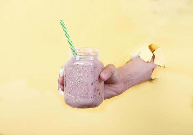 La main d'un homme tient un smoothie frais à base de lait et de cerises dans un bocal en verre
