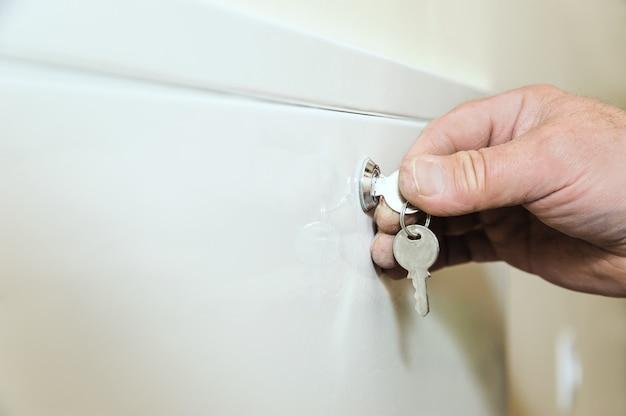 La main de l'homme tient et tourne une clé.