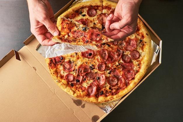 La main de l'homme tient une tranche de pizza au fromage double provenant d'un plateau à pizza entier avec un fond de table sombre.