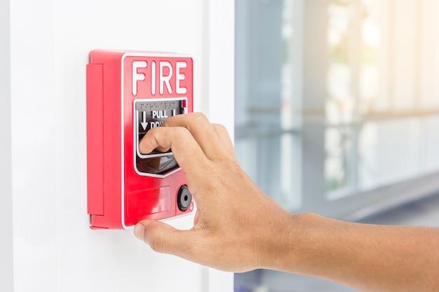 Main d'homme tirant sur l'alarme incendie sur le mur blanc comme toile de fond pour un cas d'urgence