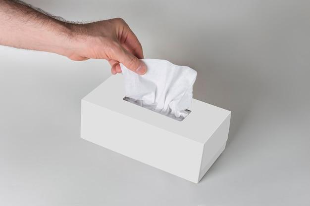 Main d'homme tirant un mouchoir dans une boîte à mouchoirs vierge blanche sur fond gris