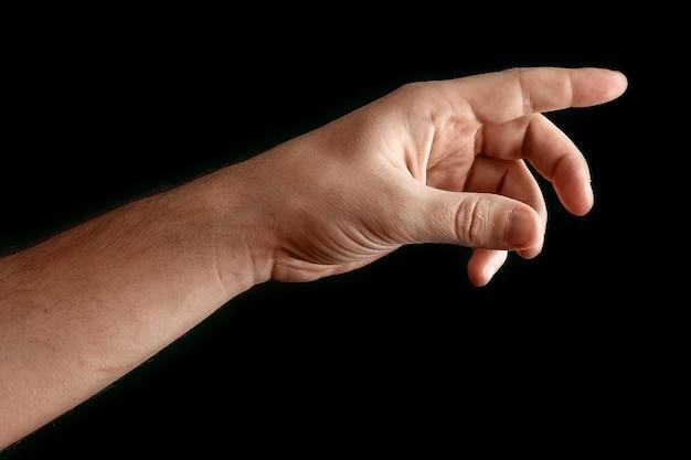 Main de l'homme touchant ou pointant vers quelque chose isolé sur fond noir