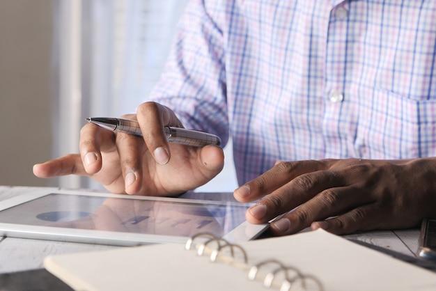 La main de l'homme travaillant sur une tablette numérique au bureau, à l'aide de graphique auto-créé.