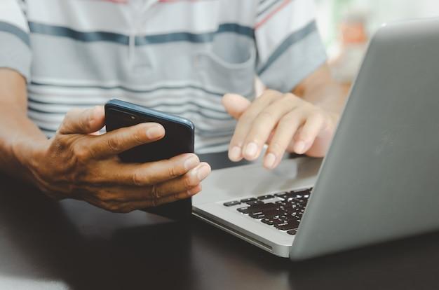 Main d'homme utilisant un téléphone intelligent et un ordinateur portable sur une table à la maison, recherchant des informations en naviguant sur internet sur le web, travaillant à domicile. concept d'achat en ligne d'entreprise