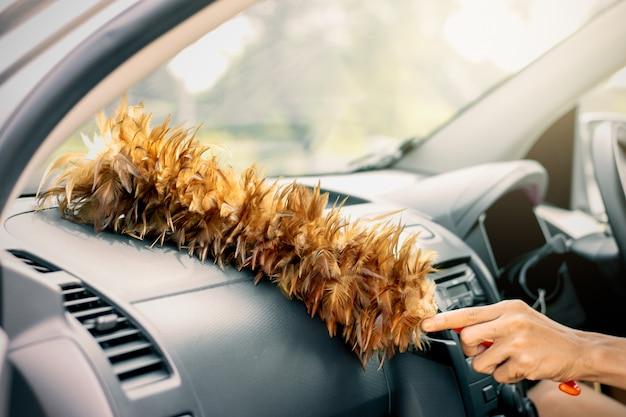 La main de l'homme utilise un balai à poulet pour nettoyer la poussière dans la voiture.