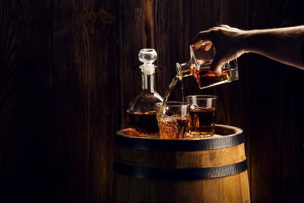Main de l'homme verse une boisson alcoolisée dans un verre