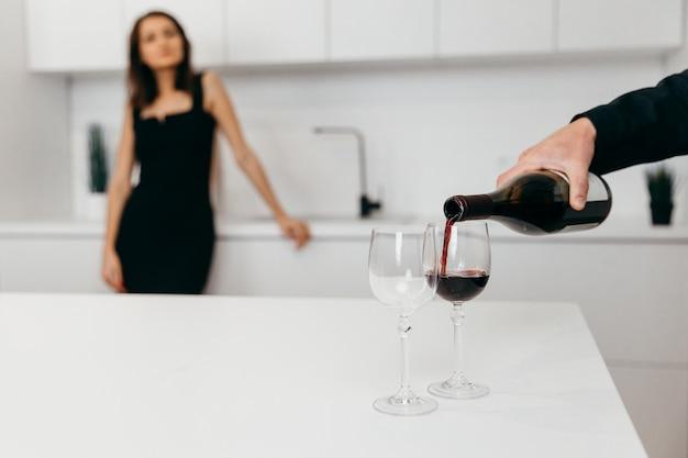 La main d'un homme verse du vin rouge dans des verres. femme en arrière-plan
