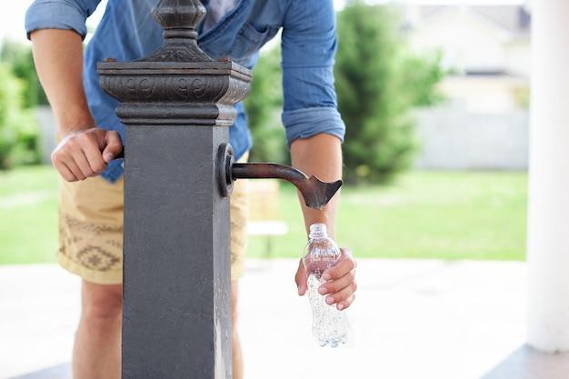 Une main d'homme verse de l'eau d'un robinet d'une colonne d'eau potable dans une bouteille en plastique