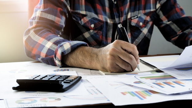 La main des hommes d'affaires sont des rapports financiers calculés par compte écrit
