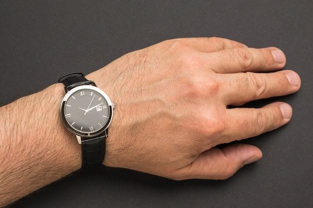 La main des hommes avec une montre-bracelet classique sur une surface noire. un accessoire pour homme à la mode et élégant.