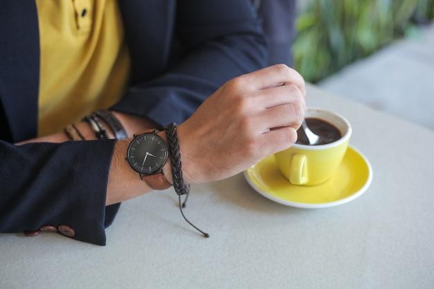 Main d'hommes portant une montre-bracelet et un bracelet en remuant le café dans une tasse