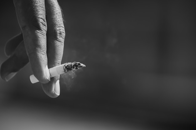 La main des hommes ramasse des cigarettes.