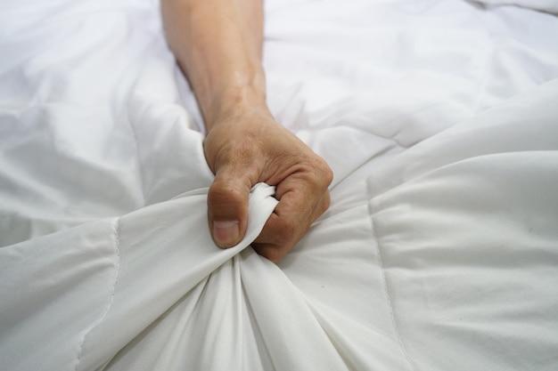 Main d'hommes tirant des draps blancs en extase, orgasme.