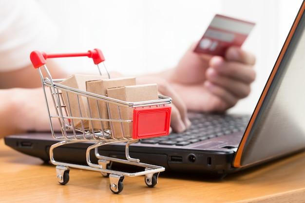 Main des hommes utilisant un ordinateur portable et acheter des marchandises auprès d'un vendeur sur internet. achats en ligne conce