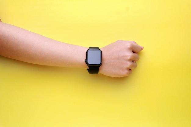 Main humaine à l'aide de smartwatch avec écran blanc sur fond jaune