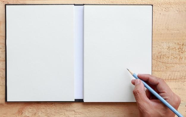 Main humaine à l'aide d'un stylo écrit sur papier