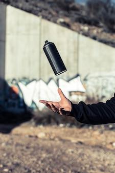 Main humaine attrapant la bombe aérosol noire