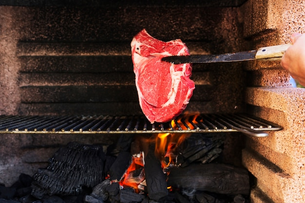 Main humaine, cuisson de la viande crue sur la grille du barbecue