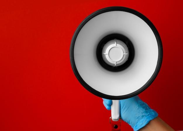 Main humaine dans un gant médical tenant un mégaphone électronique sur rouge