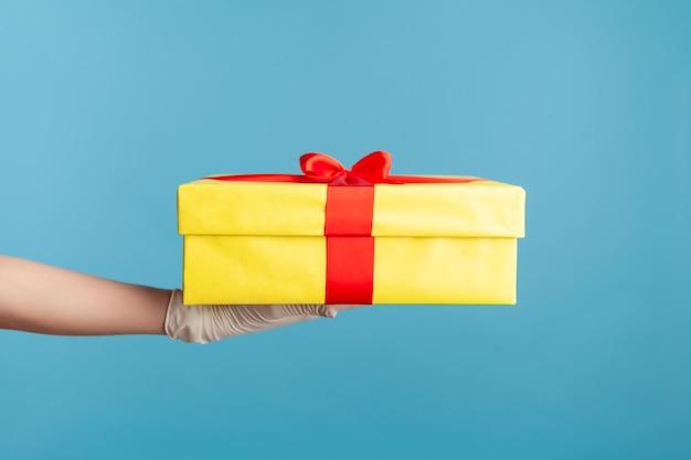 Main humaine dans des gants chirurgicaux blancs tenant une boîte cadeau jaune.