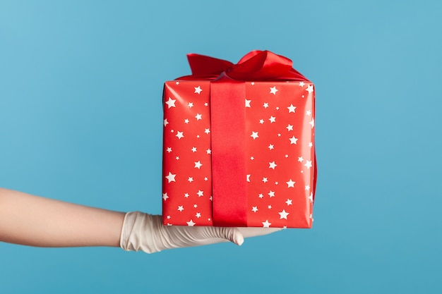 Main humaine dans des gants chirurgicaux blancs tenant une boîte cadeau rouge. concept de partage, de don ou de livraison.