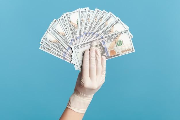 Main humaine dans des gants chirurgicaux blancs tenant et montrant un fan d'argent en dollars américains à la main.