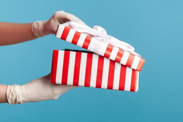 Main humaine dans des gants chirurgicaux blancs tenant et ouvrant une boîte cadeau à rayures blanches rouges.