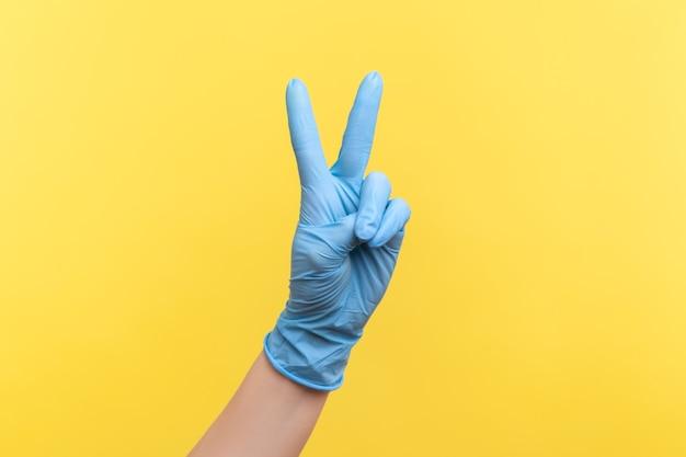 Main humaine dans des gants chirurgicaux bleus montrant la victoire, le signe de paix ou le numéro 2 avec les doigts.