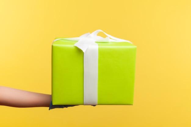 Main humaine dans des gants chirurgicaux bleus tenant une boîte-cadeau. concept de partage, de don ou de livraison