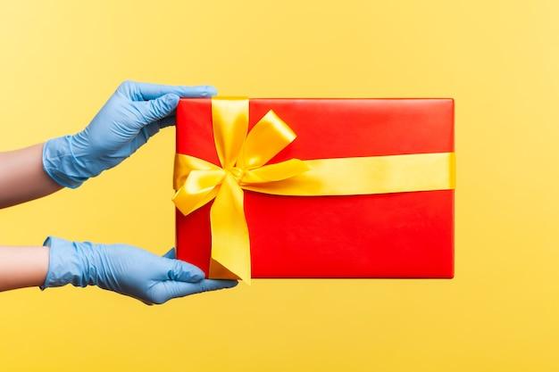 Main humaine dans des gants chirurgicaux bleus tenant une boîte cadeau rouge. concept de partage, de don ou de livraison.