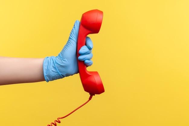 Main humaine dans des gants chirurgicaux bleus tenant et montrant le récepteur de combiné téléphonique d'appel rouge.