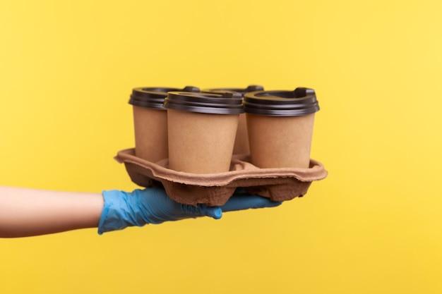 Main humaine dans des gants chirurgicaux bleus tenant et montrant des tasses de boisson chaude à emporter à la main.