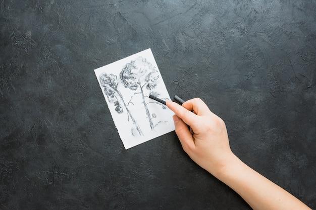 Main humaine en dessin avec un bâton de charbon de bois sur fond noir