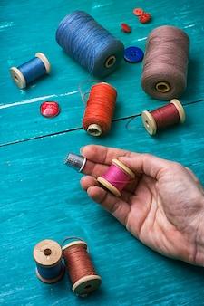 Main humaine et fil avec des boutons sur un fond en bois turquoise