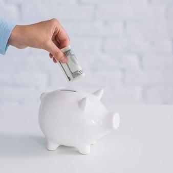 Main humaine en insérant un billet de banque dans une tirelire blanche sur le bureau
