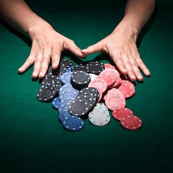 Main humaine avec des jetons de casino sur la table de poker