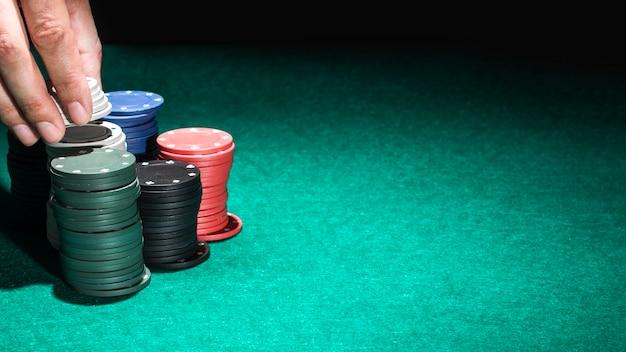 Main humaine avec des jetons de casino sur la table verte