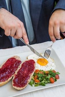 Main humaine, manger le petit déjeuner au restaurant