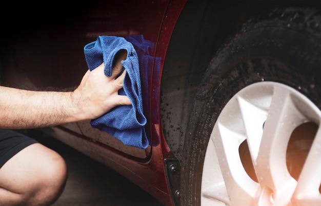 Main humaine nettoyant une voiture sale avec un chiffon en microfibre se bouchent