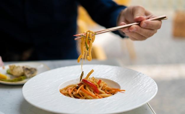 Main humaine qui soulève l'udon aux légumes avec des baguettes