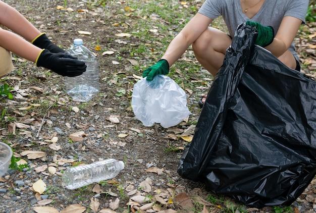 La main humaine récupère les déchets plastiques dans des sacs poubelles pour l'environnement