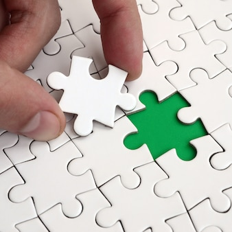 La main humaine remplit les derniers éléments manquants de la surface du puzzle.