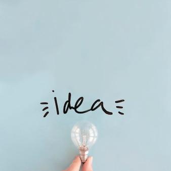 Main humaine tenant l'ampoule près de mot d'idée