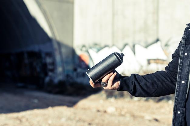 Main humaine tenant une bombe aérosol noire