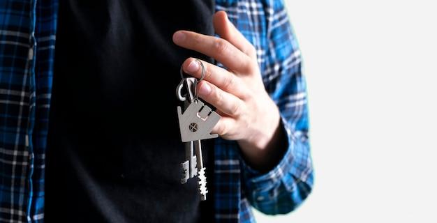 Une main humaine tenant une clé de la maison symbole de l'achat d'un appartement