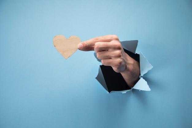 Main humaine tenant un coeur en bois sur une scène bleue