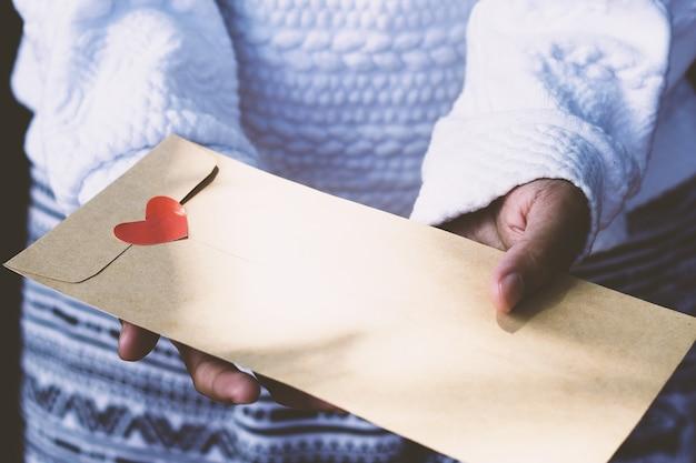 Main humaine tenant une enveloppe brune décorée d'un coeur rouge regardez de près
