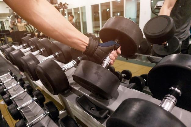 Main humaine tenant des haltères dans une salle de sport